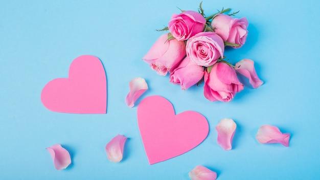 Rosas rosas con corazones en mesa.