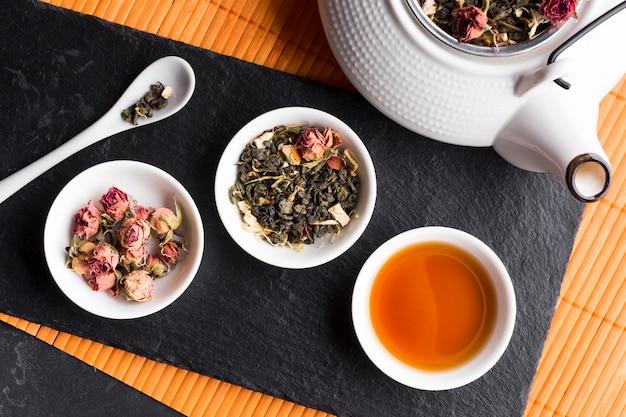 Rosas secas y hierba de té con tetera sobre pizarra negra sobre mantel