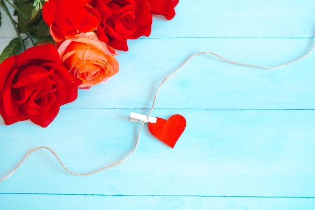 Rosas sobre fondo azul y corazones atrapados por hilo. fondo de san valentín