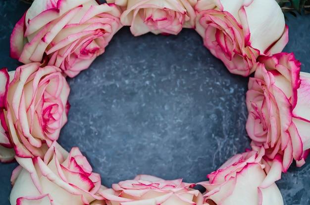 Rosas sobre fondo de mármol oscuro con lugar para el texto. lay flat