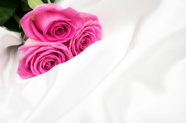 Rosas sobre fondo de seda blanca.