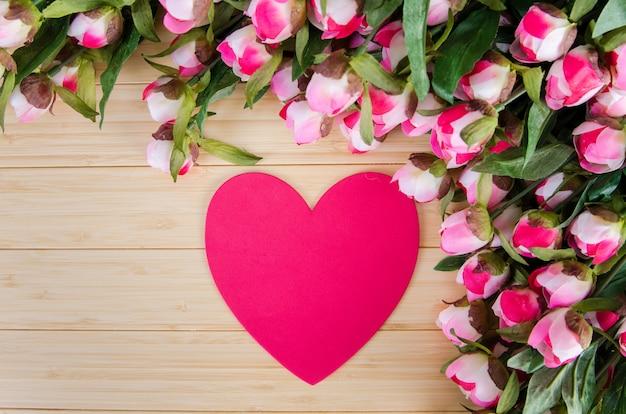 Rosas y tarjeta con forma de corazón para tu mensaje.