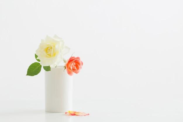 Rosas en taza blanca sobre mesa de madera blanca