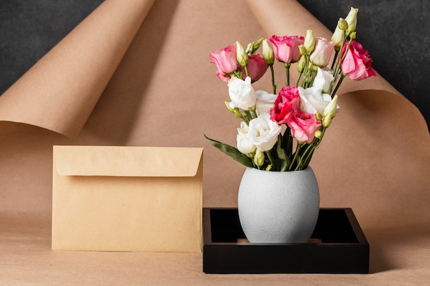 Rosas de vista frontal en composición de florero con sobre