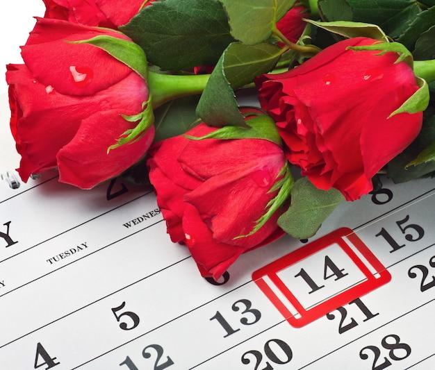 Las rosas yacían en un calendario con la fecha del 14 de febrero día de san valentín