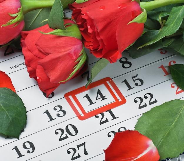 Las rosas yacían en el calendario con la fecha del 14 de febrero día de san valentín