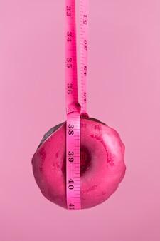 Rosquilla rosa con cinta métrica