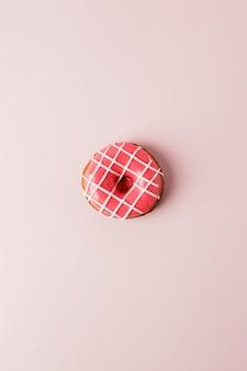 Una rosquilla rosada en vivo sobre fondo rosa, concepto de alimentos insalubres de seet monocromos, endecha plana
