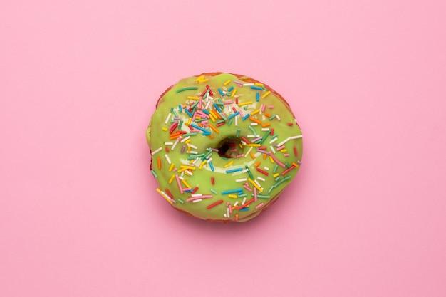 Rosquilla verde dulce con espolvorear sobre un fondo rosa plano lay
