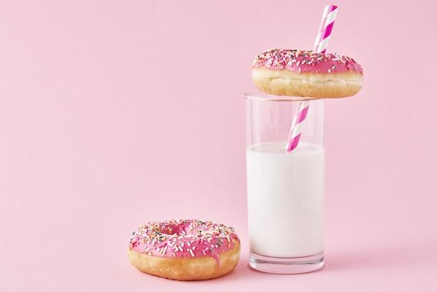 Rosquillas decoradas con glaseado y espolvorear y vaso de leche.