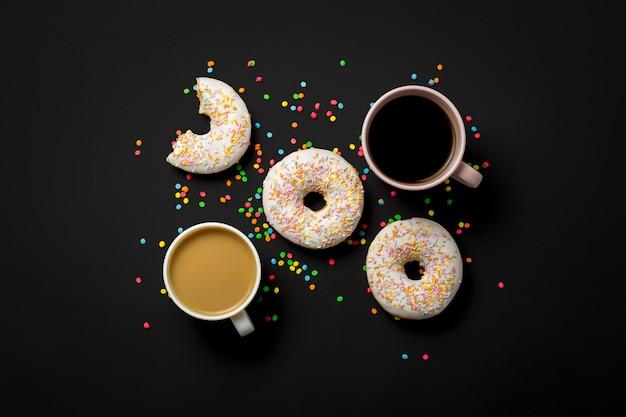 Rosquillas deliciosas, dulces y frescas, caramelos decorativos multicolores, una taza de café sobre un fondo negro. concepto de desayuno, comida rápida, cafetería, panadería. vista plana, vista superior.