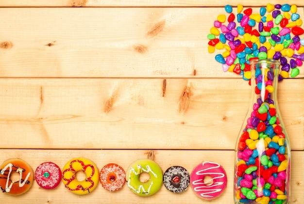 Rosquillas dulces color pastel sobre fondo de madera