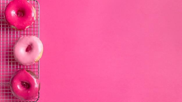 Rosquillas dulces de color rosa con espacio de copia