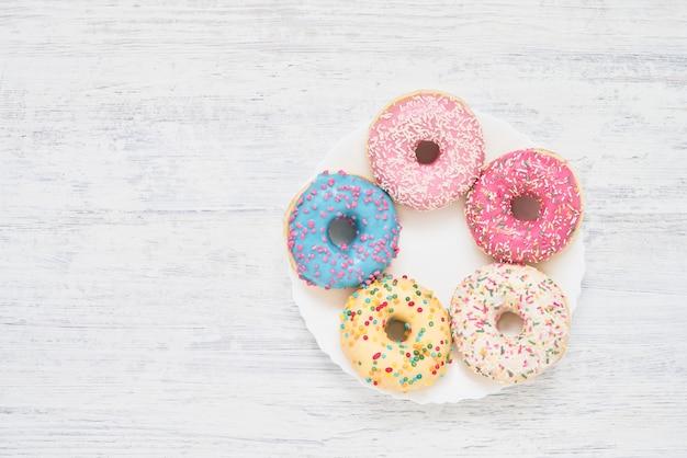 Rosquillas dulces y coloridas en el plato blanco sobre la mesa