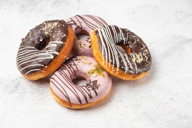 Rosquillas glaseadas de chocolate y rosa sobre superficie de mármol.