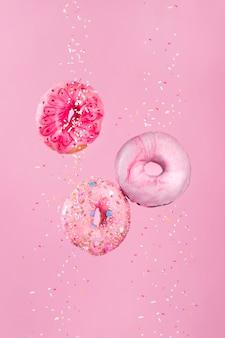 Rosquillas glaseadas rosas en movimiento