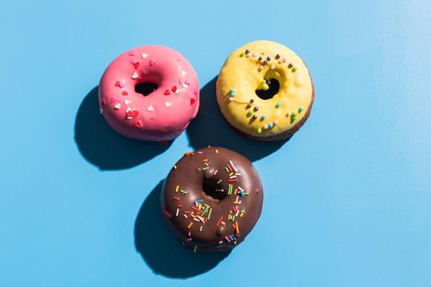 Rosquillas redondas coloridas en el fondo azul brillante. rosquillas dulces. luz solar de moda patrón de verano concepto mínimo de verano.