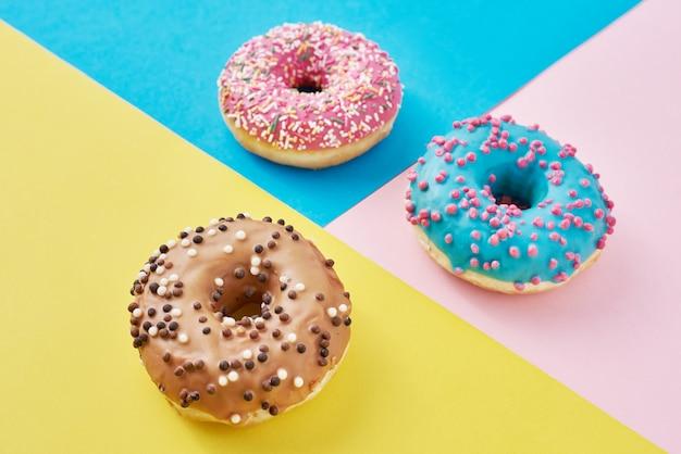 Rosquillas en rosa pastel, amarillo y azul. minimalismo composición creativa de alimentos. estilo plano laico