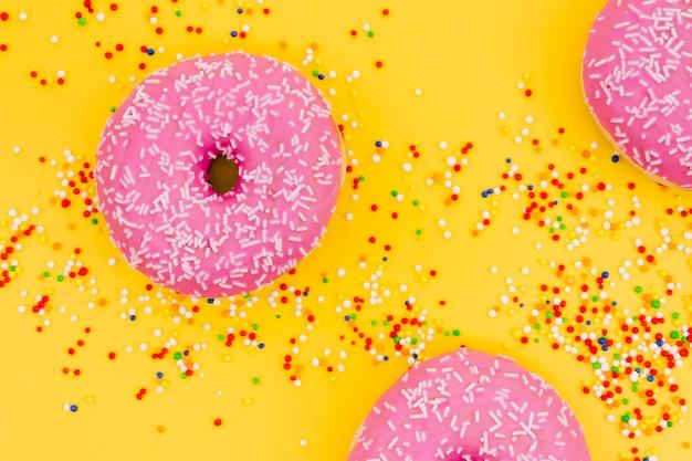 Rosquillas rosadas con colorido asperjan sobre fondo amarillo
