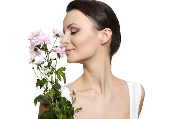Rostro de belleza de la joven bella mujer con flores de colores aislados en blanco