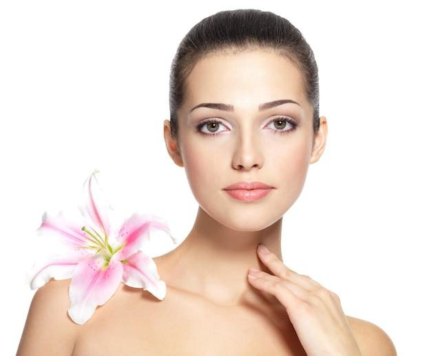 Rostro de belleza de mujer joven con flor.