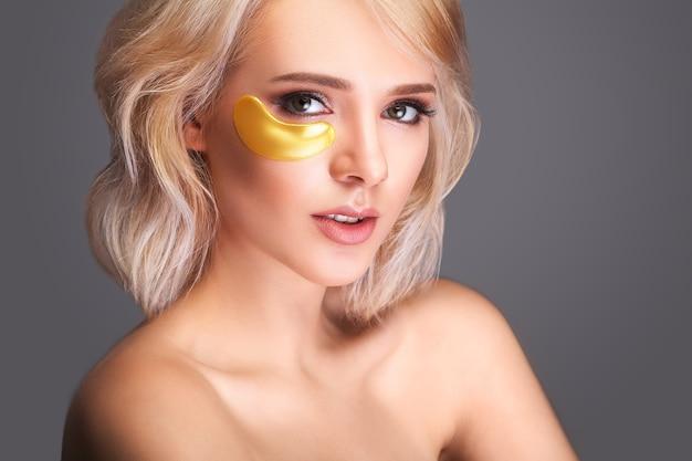 Rostro de belleza de mujer con máscara debajo de los ojos. hermosa mujer con maquillaje natural y parches de colágeno dorado en la piel facial fresca.