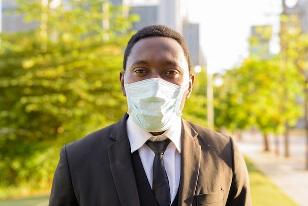 Rostro del empresario africano con máscara en el parque de la ciudad