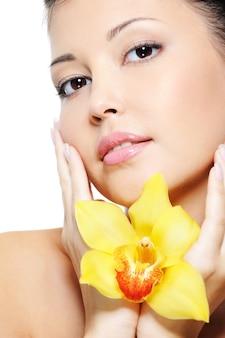 Rostro femenino asiático de sensualidad atractiva con flor en las manos