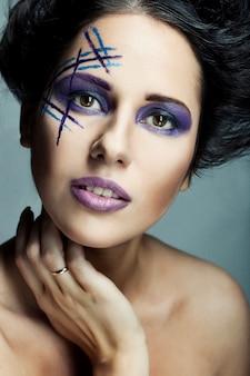 Rostro femenino joven con maquillaje multicolor de moda brillante
