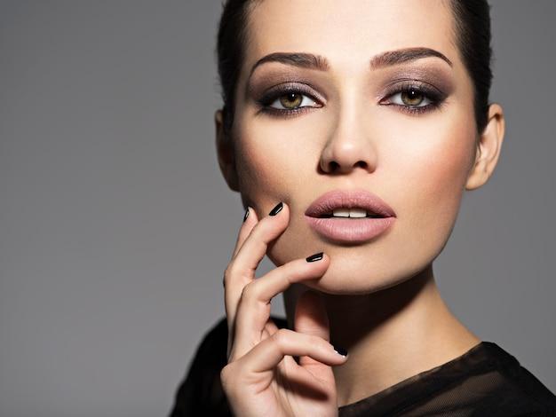 Rostro de una hermosa niña con maquillaje de moda y uñas negras posando sobre pared oscura