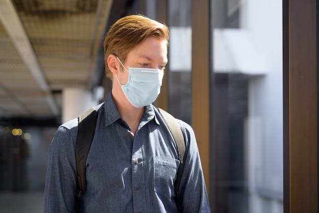 Rostro de hombre joven turista estresado con máscara pensando en el aeropuerto