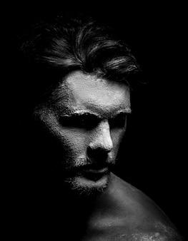 Rostro de hombre con máscara blanca en la oscuridad