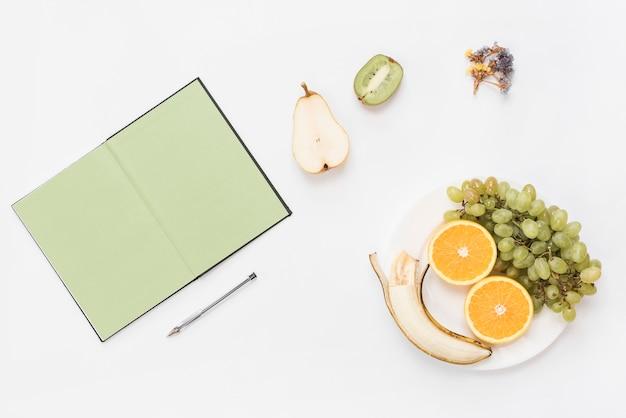 Rostro humano sonriente hecho con frutas en el plato; libro y pluma aislados sobre fondo blanco