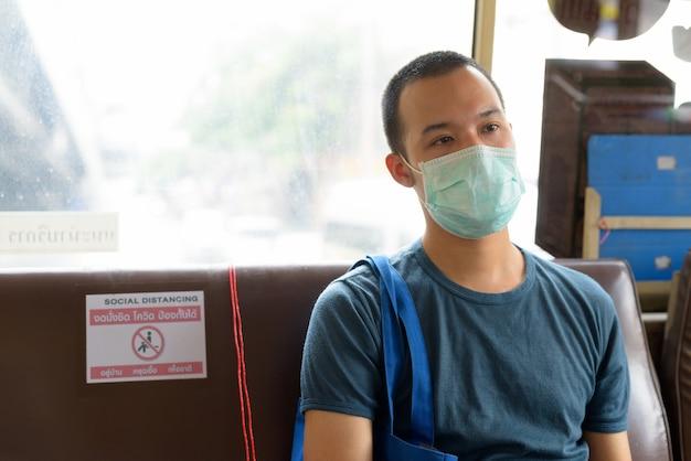 Rostro de joven asiático con máscara en el autobús con distancia