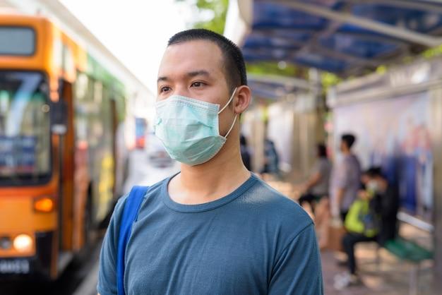 Rostro de joven asiático con máscara para protegerse del brote de coronavirus en la parada de autobús
