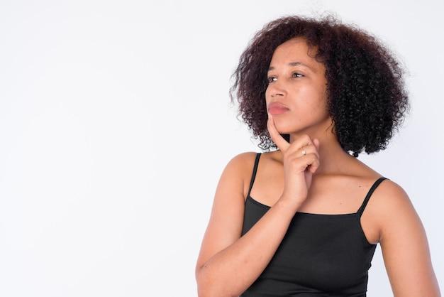 Rostro de joven hermosa mujer africana pensando y mirando hacia arriba