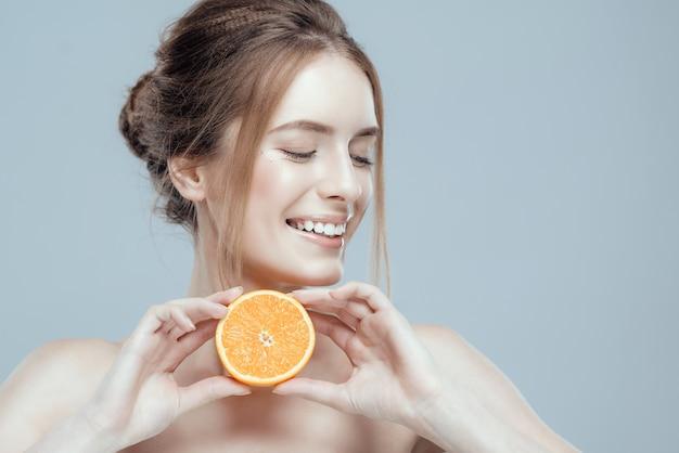 Rostro joven con naranja jugosa