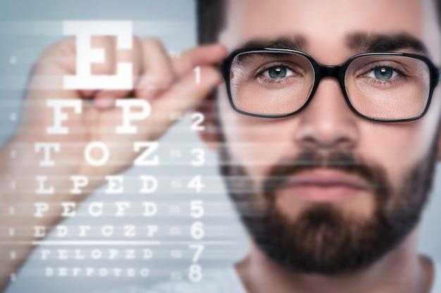 Rostro masculino y tabla optométrica