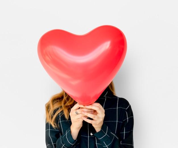 Rostro de mujer adulta joven cubierta con globo de corazón