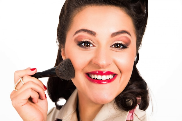 Rostro de mujer feliz con un cepillo para polvo