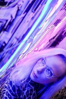 Rostro de mujer con gafas en montura metálica que reflejan luz neón, selec.
