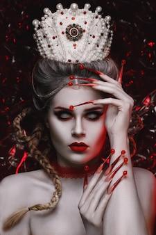 Rostro de mujer hermosa con maquillaje de moda creativa y con largas uñas rojas.