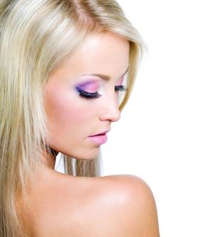 Rostro de mujer hermosa con maquillaje saturado
