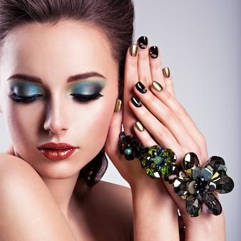 Rostro de mujer hermosa con maquillaje verde y joyas de vidrio, uñas creativas