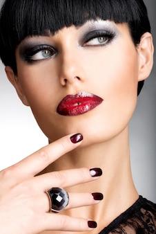Rostro de una mujer con hermosas uñas oscuras y sexy labios rojos. modelo de moda con pelos de tiro negro