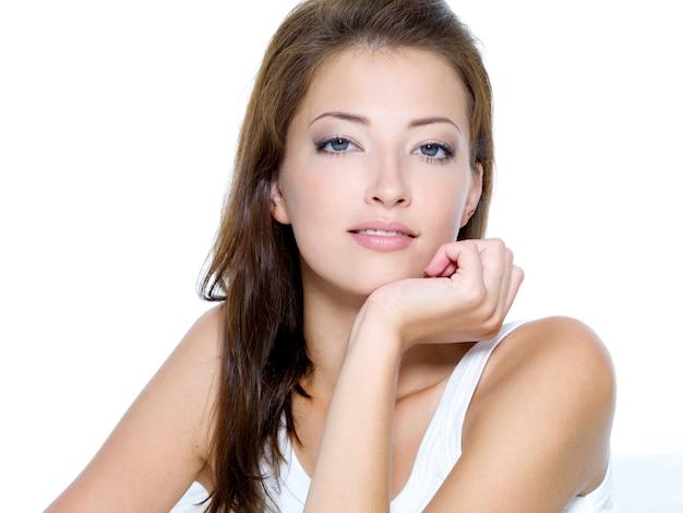 Rostro de una mujer joven hermosa sexy con la piel limpia en un espacio en blanco