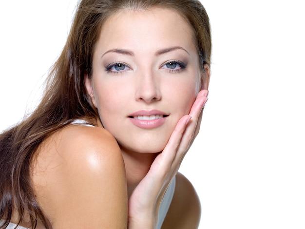 Rostro de una mujer joven hermosa sexy con la piel limpia sobre un fondo blanco