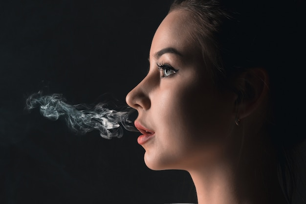 El rostro de una mujer joven vaping en el estudio negro