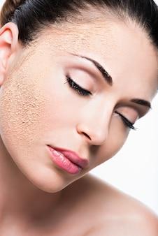 Rostro de mujer con polvo cosmético en la piel