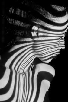 El rostro de una mujer con rayas de cebra en blanco y negro